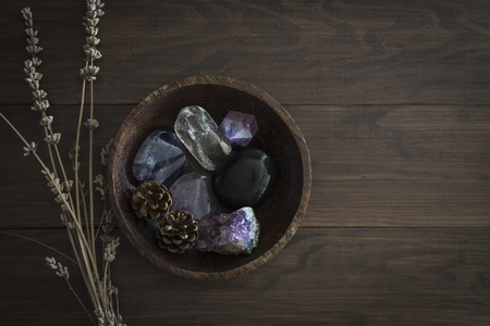 Wooden bowl with selection of stones and crystals on table