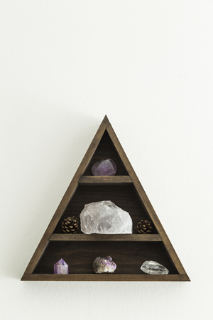 Wooden triangular crystal shelf with stones and pine cones hung on wall