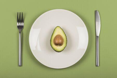 Medio aguacate en un plato blanco con cuchillo y tenedor con un fondo verde. Foto de archivo