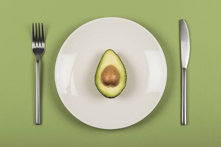 Pół awokado na białym talerzu z nożem i widelcem na zielonym tle. Zdjęcie Seryjne