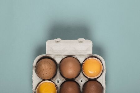 Six eggs in an egg box on a blue background.