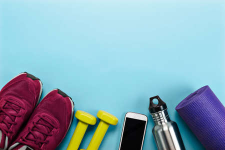Sports equipment including running shoes, yoga mat, water bottle and cellphone.