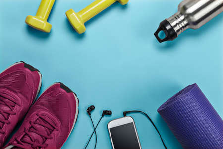 Equipment for sports, yoga and gym classes, with running shoes, weights, yoga mat, water bottle and mobile phone. 免版税图像
