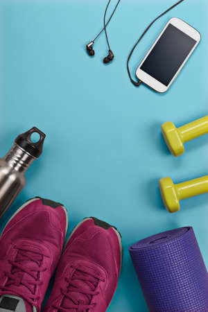 Rolled yoga mat and sports shoes with weights, water bottle and cellphone arranged in a flat lay view with copy space in the middle. 免版税图像