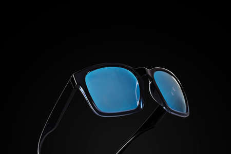 Pair of black sunglasses with blue tinted frames on dark background 免版税图像