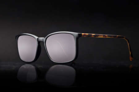 A pair of sunglasses with black and tortoiseshell effect frames on a dark background. 免版税图像