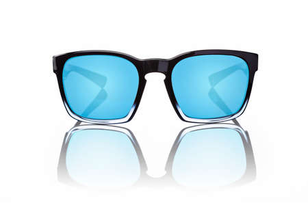 Pair of sunglasses with blue tinted lenses and black frames on white background with reflection, shot directly from the front. 免版税图像
