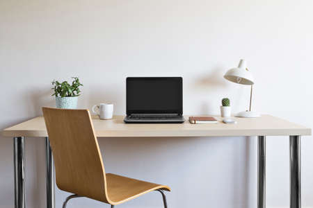 Wooden desk with chair, laptop, plants, coffee mug, journal, cellphone and lamp.