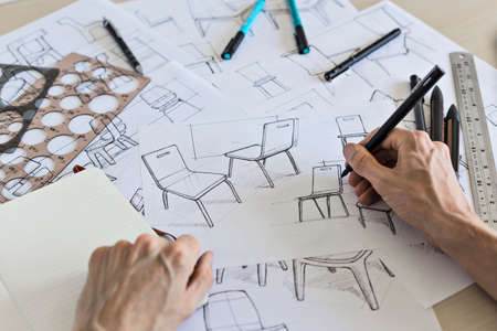 Product designer sketching concepts for a chair with pens and drawing instruments on a desk in the design studio.