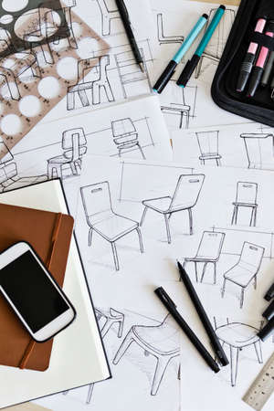 Product designers desk with design sketches and drawing instruments, including ruler, markers and guides. 免版税图像