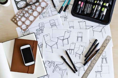 Selection of product design sketches on a desk with drawing implements, such as pens, markers and guides.