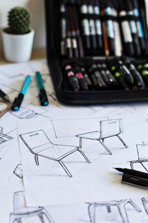 Sketches on a designers desk with pens, pencils, markers and other drawing instruments.