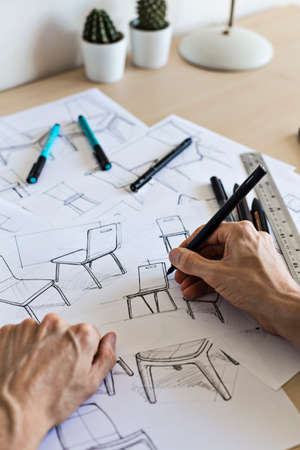 Industrial designer sketching ideas for a chair concept at a desk in a design studio.