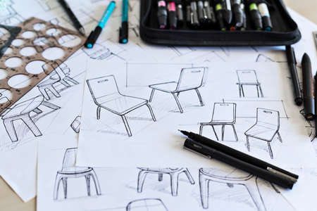 Product design sketching with pens, pencils and drawing instruments on a design studio desk.