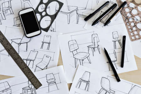 Sketching of ideas for chair designs with drawing implements such as pens, markers, ruler and circle and ellipse guides. 免版税图像