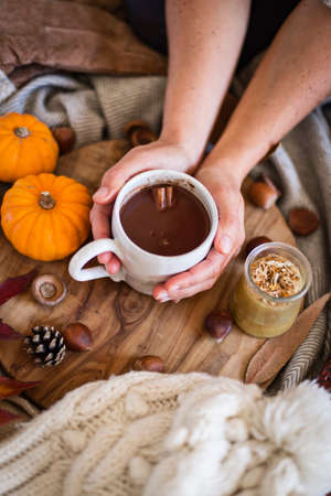 Woman holding mug of hot chocolate with both hands during autumn
