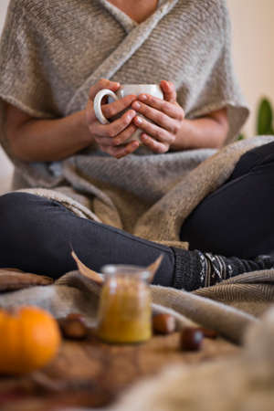 Woman wearing warm cosy clothes holding mug of hot chocolate in hands in autumn
