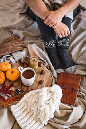 Woman in cozy warm clothes sat next to wooden board with cup of hot chocolate and autumnal objects