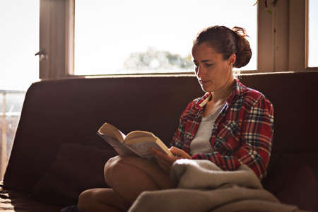 Woman in pyjamas relaxing and reading a book on brown couch in the morning at the weekend.