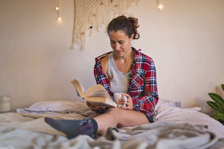Woman in pyjamas on bed reading book and drinking a mug of tea.