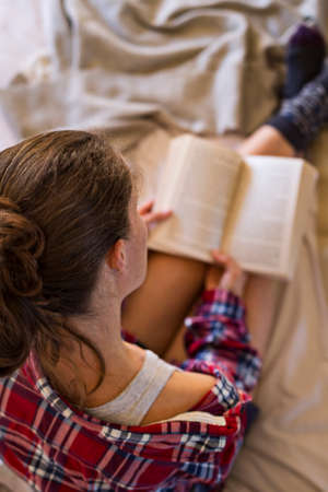 Woman in pyjamas reading book on bed having a lazy morning