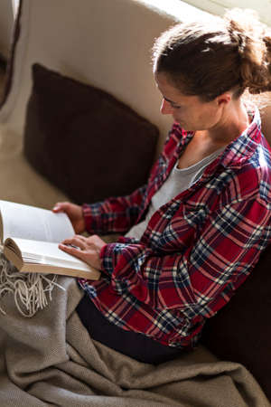 Relaxed woman in red shirt and pyjamas reading a book on couch on a lazy weekend morning