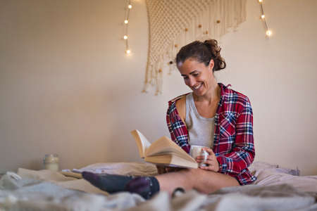 Smiling woman reading book in pyjamas and enjoying lazy morning in bed 免版税图像