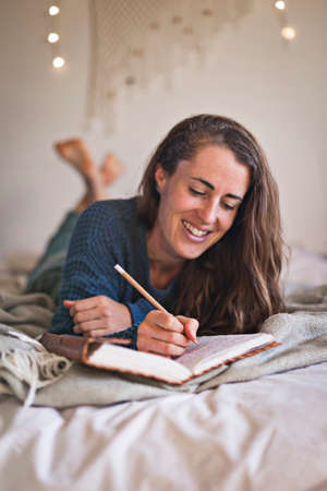 Woman lying on her bed writing in her leatherbound notebook. 免版税图像