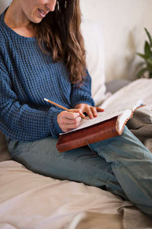 Woman sat writing in her leatherbound journal in bed.