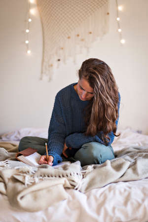 Woman in blue sweater sat on bed writing in her leatherbound journal with a pencil