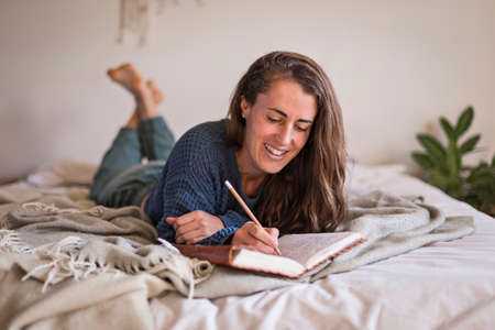 Woman in blue sweater lying on her bed writing in her leatherbound journal 免版税图像