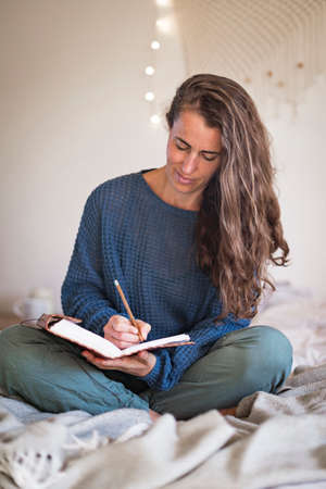 Woman in blue sweater writing in leatherbound journal whilst sat on her bed