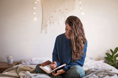Woman in blue sweater sat on her bed writing in her leatherbound journal