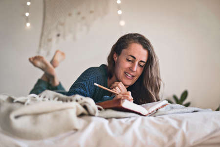 Woman writing in her leatherbound diary whilst lying on bed with fairy lights in background.