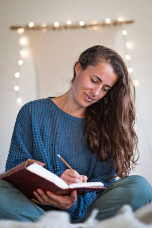Woman in blue sweater making notes in her leatherbound journal