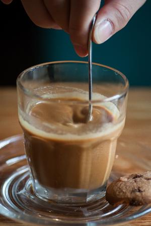 milk coffee stirring by a spoon in a glass