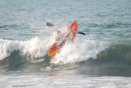 Sayulita Mexico is a surfers paradise known for its long breaks.  This Sit on top kayaker punches a cresting wave on his way past the break.