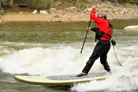 dry suit: A stand up paddleboard surfer frozen in time using a slow shutter speed as the river flows past. Stock Photo