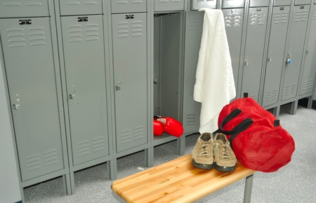 Locker room with boxing gloves in focus,  shoes and gym out of focus. photo