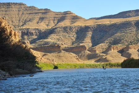 a kayaker and paddleboarder are slihouetted against a steep canyon wall.