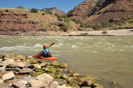 A lone kayaker paddling with canyon walls in the background. photo