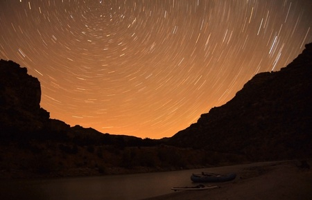 Star swirls in Northern sky with a raft and paddleboard in foreground.