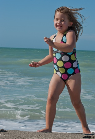 Cute young girl running from the ocean 写真素材