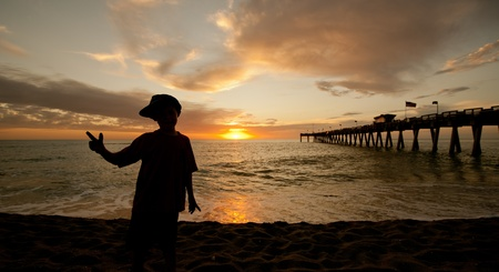 A young boy holding a peace sign, silhouetted against an orange sunset