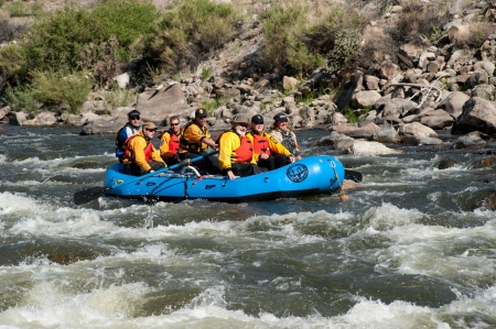 CANON CITY, CO/USA - MAY 19, 2012: Colorado State Governor John Hickenlooper (center with CR hat)  rafts the site of the Jean Claude/Cristo Over The River project.