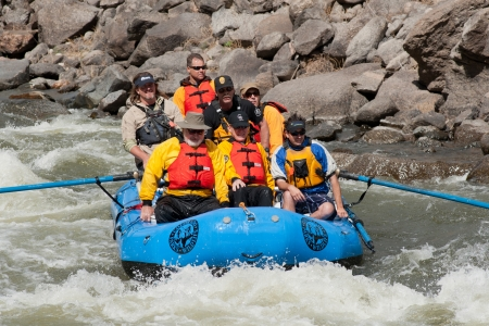 CANON CITY, COUSA - MAY 19, 2012: Colorado State Governor John Hickenlooper (center with CR hat)  rafts the site of the Jean ClaudeCristo Over The River project.