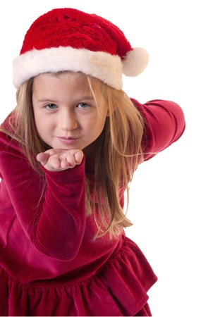 white isolation of young girl wearing santa hat blowing a kiss