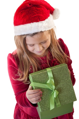 White isolation of young girl wearing santa hat opening present photo