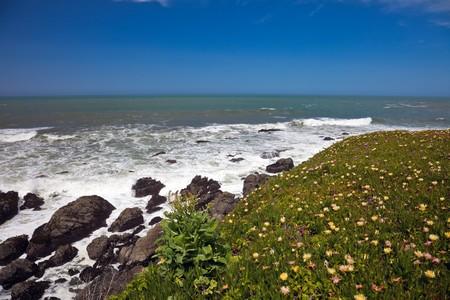 breading: Scenic view of waves breading on rocky ocean coastline under blue skies. Stock Photo