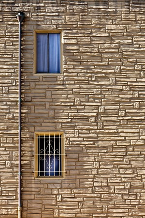 nonuniform: Stone wall.  Fragment of a Stone Wall with Windows and Downspout. Stock Photo